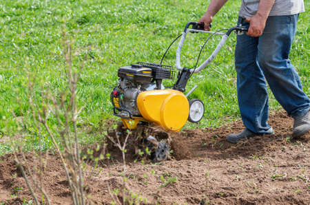 Man Farmer plows the land with a cultivator. Agricultural machinery: cultivator for tillage in the garden,motor cultivator.