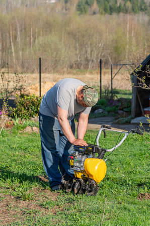 A male farmer prepares a cultivator for work. Agricultural machinery: cultivator for cultivating soil in the garden, motor cultivator.
