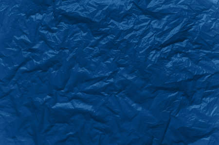 Abstract background in blue. Crumpled plastic surface. Top view.