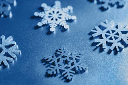 Christmas decorative snowflakes toned blue. Selective focus. Close up. Фото со стока
