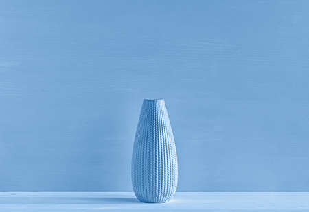 Ceramic vase on a blue background. The concept of minimalism. Close up.