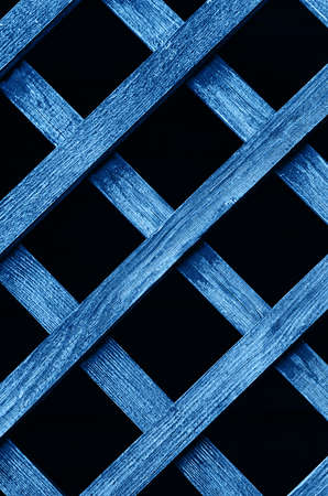 Wooden fence lattice toned blue. Wood grating close up. Abstract wood texture. Vertical frame. Фото со стока