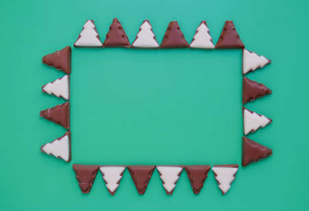 Pattern of chocolate Christmas trees. Rectangular frame. Minimalistic christmas background. Flat lay. Copy spase. Top view. Фото со стока