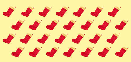 Pattern made of christmas boots on a yellow background. Flat lay, top view.