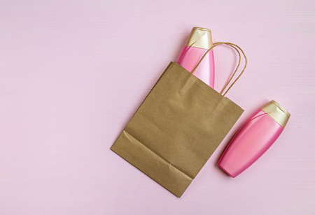 Blank brown paper bag, empty cosmetic bottles on a pink background for print design and mock up. Flat lay. Copy space.