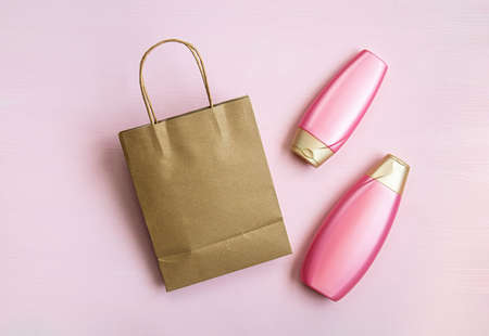 Blank brown paper bag, empty cosmetic bottles on a pink background for print design and mock up. Flat lay.
