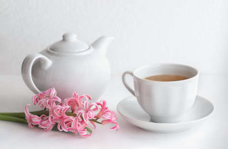 White ceramic teapot and cup with tea. Hyacinth flower on a white background. Selective focus. Breakfast concept. Close up. Stockfoto