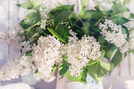 A bouquet of white lilac in an old vintage jug. Spring floral background. Selective focus. Close up.