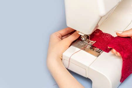 Sewing process on sewing manufacturing machine detailed by woman's hands holding red lace fabric for lingerie production. Copy space. Close up. Standard-Bild