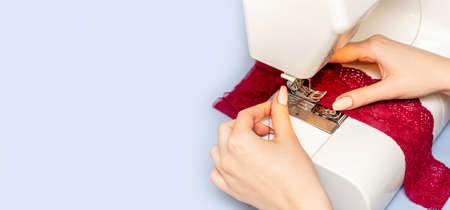 Sewing process on sewing manufacturing machine detailed by woman's hands holding red lace fabric for lingerie production.