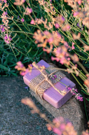 Handmade soap on a background of blooming lavender. Floral background. Vertical crop.