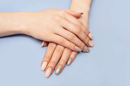 Beautiful well-groomed hands with manicure and nail polish. Blue pastel background. Close up. Фото со стока