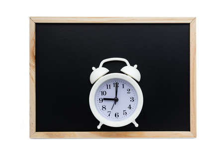White alarm clock on the background of a black school board. The concept of the beginning of the school year. Flat lay.