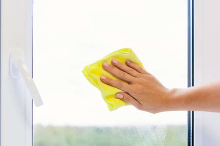 Washing a window pane with a yellow microfiber cloth, close-up with a blurred background. Autumn or spring cleaning concept.
