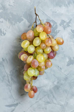 A branch of ripe yellow grapes on a gray concrete background. Close up. Top view. Copy space. Vertical crop.