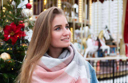 Happy young blonde girl on the background of the Christmas market. New Year's mood in the big city. Christmas or New Year concept.