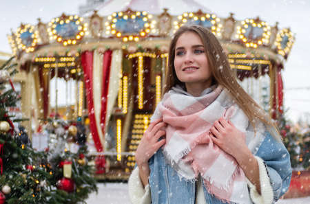 Girl walking in Christmas market decorated with holiday lights. Feeling happy in big city. Christmas or New Year concept.