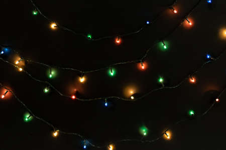 Christmas garland with bright colorful lights on a black background. Festive Christmas background. Top view.