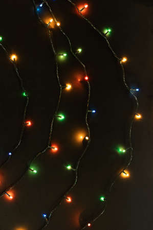 Christmas garland with bright colorful lights on a black background. Festive Christmas background. Vertical crop.