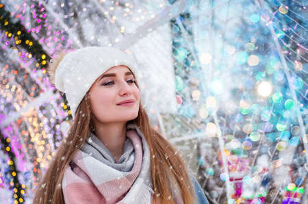 Young beautiful girl smiling on the background of Christmas lights. Winter holiday and Christmas concept. Close up.