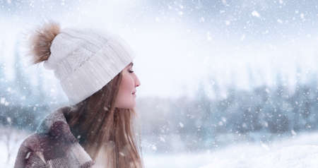 A beautiful young girl stands with closed eyes against the background of a winter forest and enjoys the first snow. Selective focus. Copy space.