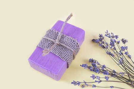 Natural handmade soaps and lavender flowers on a light yellow background. Close up. 免版税图像