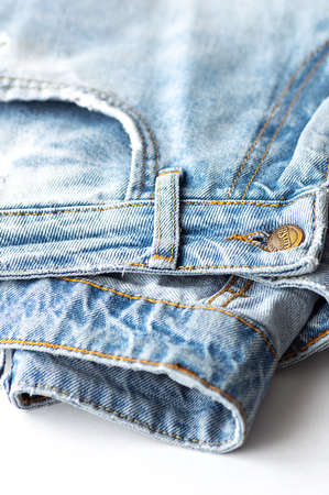 Blue jeans on a white background. The texture of the cotton fabric. Close up. Vertical crop.