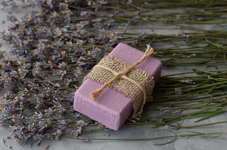 Handmade soap with natural ingredients and dry lavender flowers on a gray concrete background. Close up.