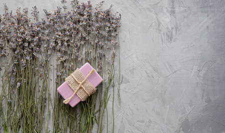 Handmade soap with natural ingredients and dry lavender flowers on a gray concrete background. Top view. Flat lay. 免版税图像