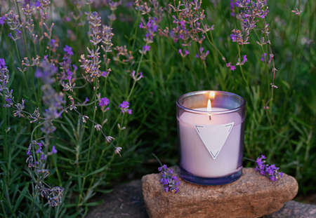 Homemade candle with herbal scent against a background of blooming lavender. Magical rituals and practices in everyday life. Selective focus.
