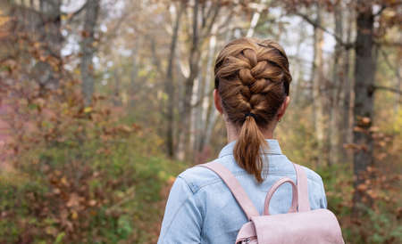 Girl in a denim shirt with a backpack on the background of the autumn forest. Close up. Back view of young woman with scythe. Copy space.