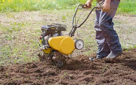 Farmer man plows the land with a cultivator. Soil preparation for sowing. Agricultural machinery for tillage in the garden.