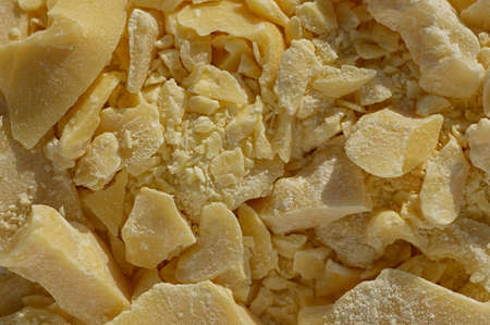 Pieces of crushed cocoa butter. Chopped cocoa oil, a natural ingredient in the pharmaceutical and medical industry. Close up.