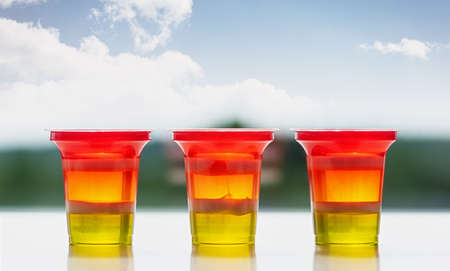 Three glasses of colorful striped jelly on a natural background. Rainbow jelly for kids party. Close up. 免版税图像