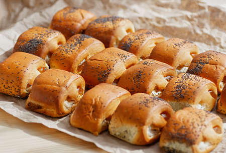 Homemade buns with fruit jam on a background of crumpled pastry paper. Selective focus. Close up. Copy space. 免版税图像