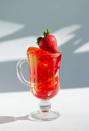 Ripe strawberries and delicious fruit jelly in a glass glass on a white background. Vertical crop. Close up. 免版税图像