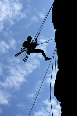 crevasse: a man-climber rises on the wall with the help of the ropes