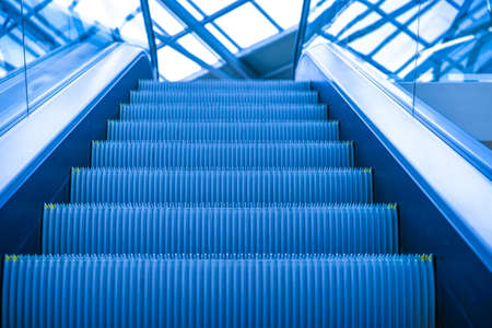 Escalator in the shopping center. The stairs to the top. Escalator with glass handrails. Upward movement.