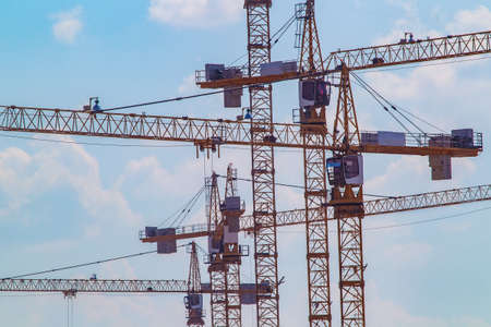 Construction cranes. Construction. Many building cranes against the sky.