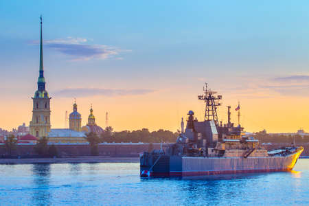 Saint Petersburg. Russia. Morning in Petersburg. The girl is looking at warships. The neva river in St. Petersburg. A warship in the background of the city. Warships in Petersburg. Vasilievsky Island.