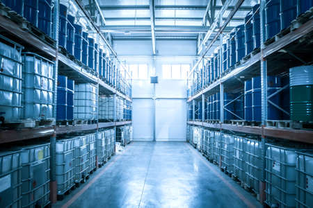 Chemical warehouse. Barrels with chemical products. Shelvings with barrels. Warehouse shelving.