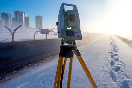 Theodolite. Topographic equipment. Theodolite takes measurements from the highway. Topographical measurements. Measurement of soil creep. Construction works.