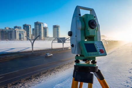 Theodolite. Surveying equipment. Theodolite stands on a tripod. Topographical measurements. Construction works. Construction measurements. The work of the tapographer.