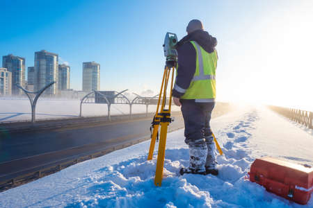 Theodolite. Topographic equipment. Theodolite stands on a tripod. Topographical measurements. Surveyor stands with a tripod. Construction works. Construction measurements. The work of the tapographer.