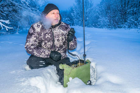 A man transmits messages by radio. Radio station with short waves. Hobby. VHF radio station. Professional KV transceiver. Winter. A man receives information on the radio.