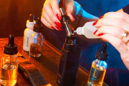 The girl is running an electronic cigarette. Fluids for Vape Zdjęcie Seryjne
