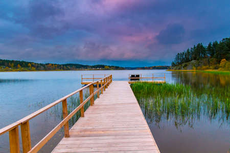 The pier on the lake. Empty dock on sunset background. A wooden bridge near the water.
