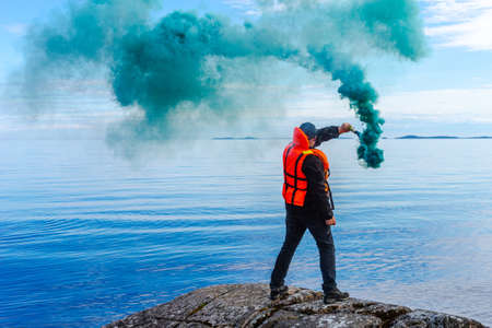 A man with a smoke torch. The rescue. Distress call. The man lights a smoke signal. A man in a life jacket. SOS. signal by smoke. 版權商用圖片
