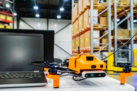 Office drone with a laptop. Warehouse equipment. Storage. Warehouse management. Drone inventory warehouse. Audit in stock. Scanning goods. Dron scans product information on the shelves.