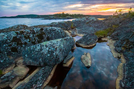 The flow between the rocks in Ladoga. Islands in the Ladoga Lake. Karelia. Russia. Nature of Karelia. Lonely pines on the rocky banks. 版權商用圖片